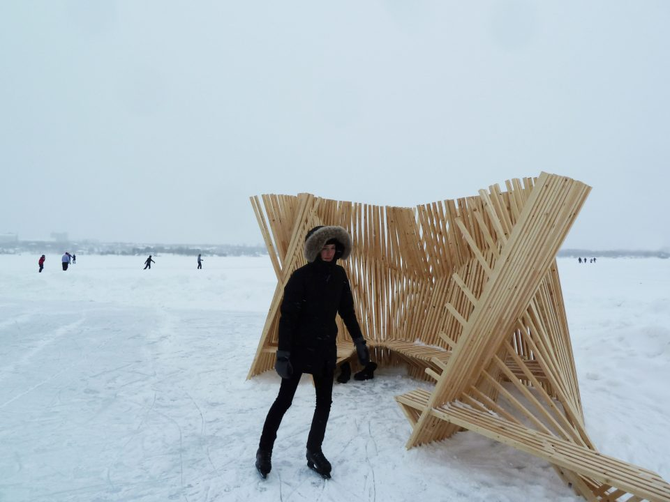 Photograph of person skating in front of a student made wooden ice station in winter