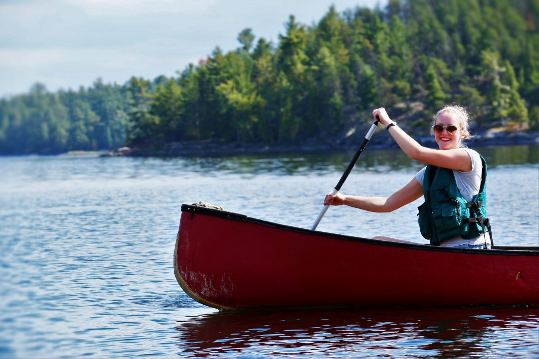 Photograph of a person rowing in a canoe