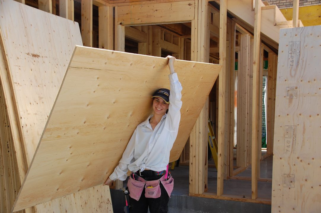 Photograph of a person carrying a piece of plywood in a woodshop