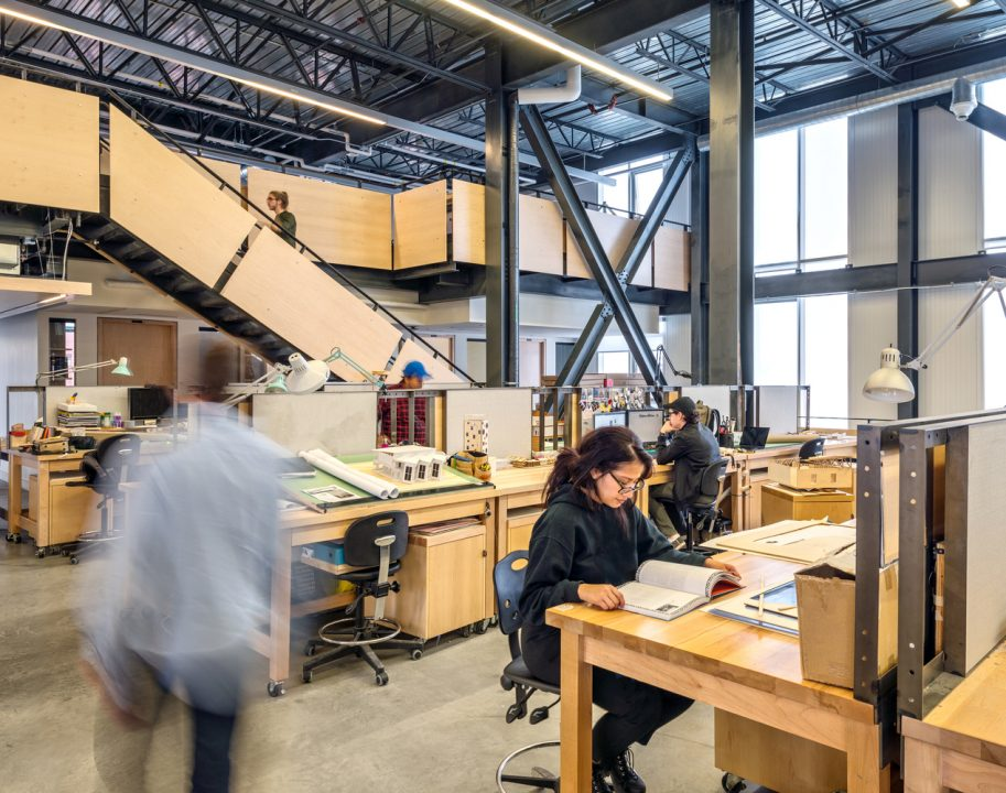 Photograph of students at their desks in a studio space