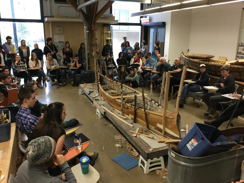 Photograph of students gathering around a half built birch bark canoe