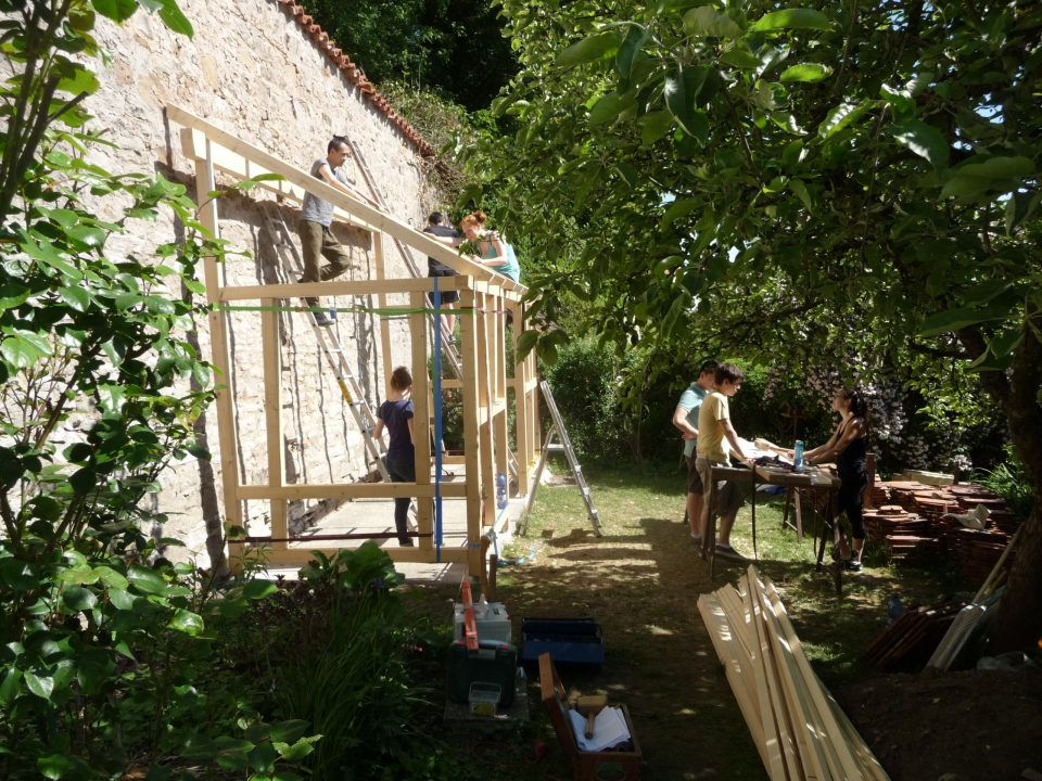 Photograph of students outside building a small shed