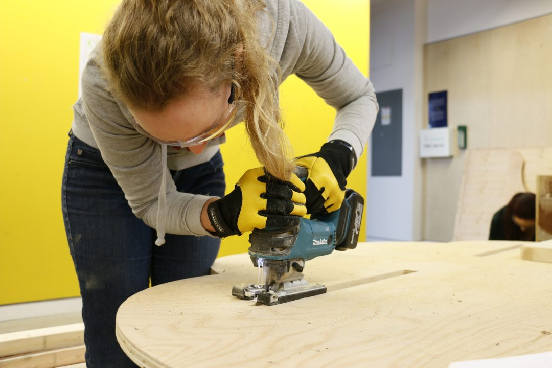 Photograph of a student using a power dry over a piece of wood