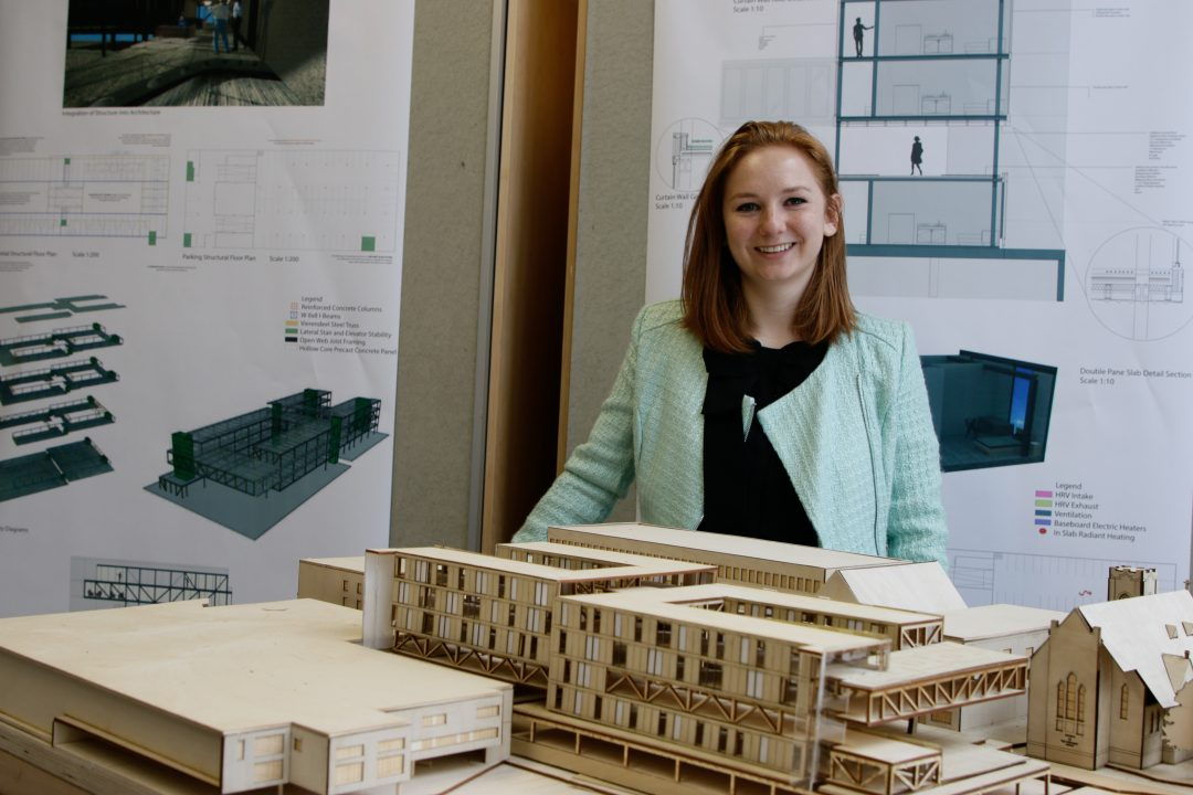 Photograph of a student smiling from behind their wooden building model