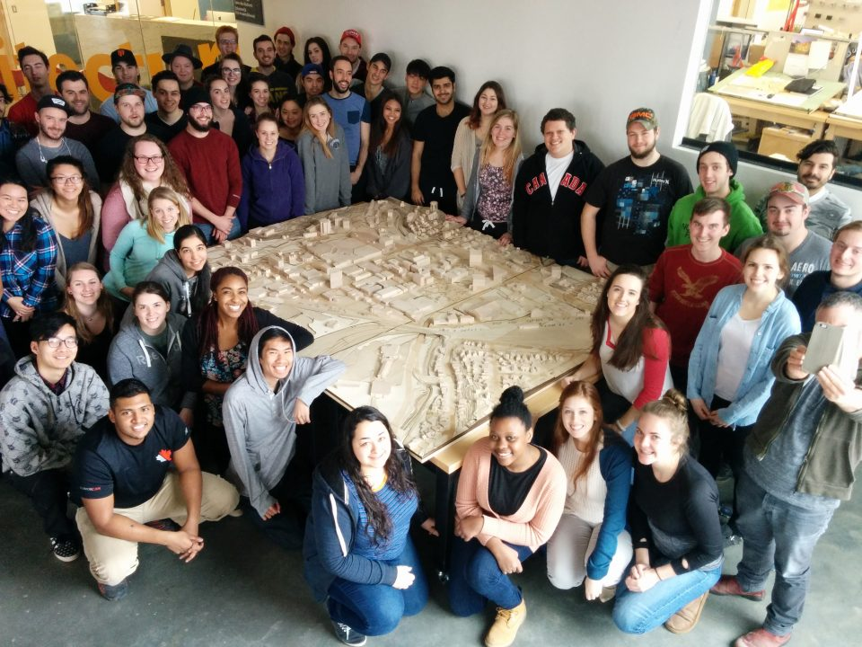 Photograph of students smiling around a large wooden city model they created