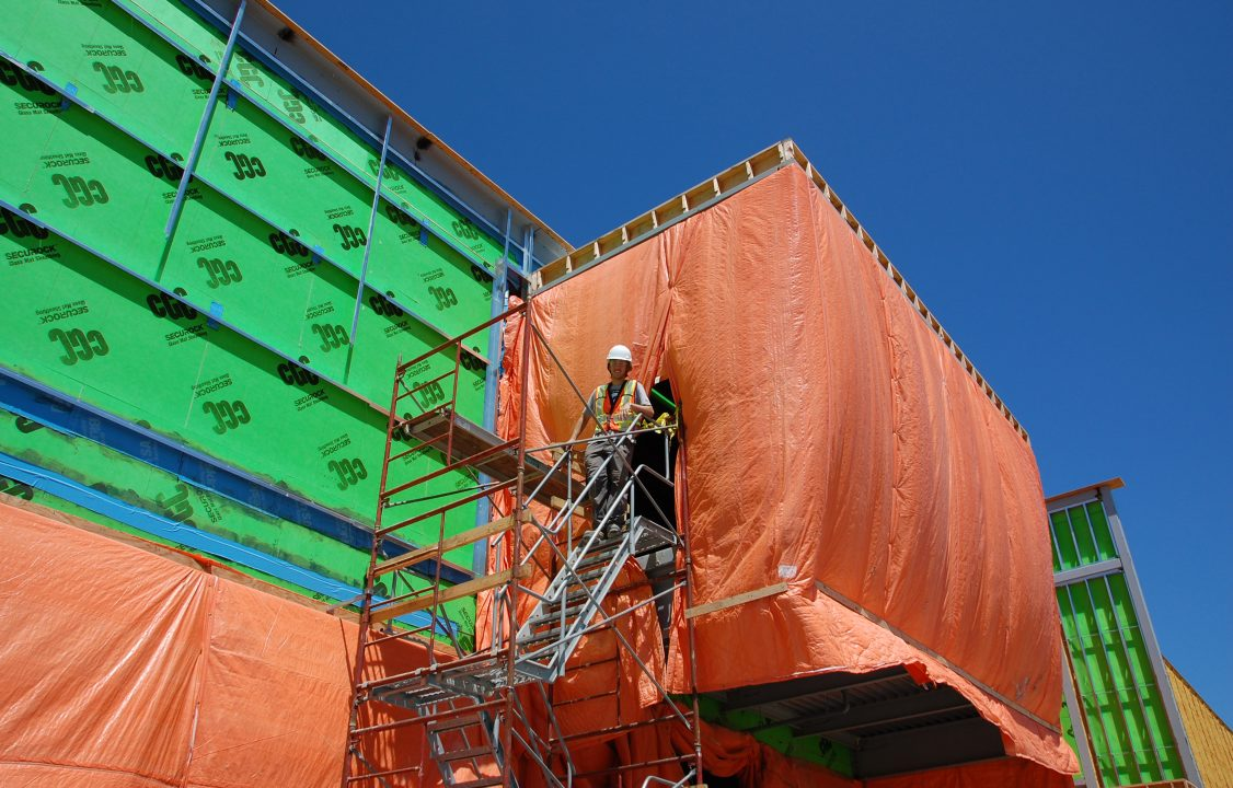 Photograph of a student smiling at the top of a set of stairs above a construction site