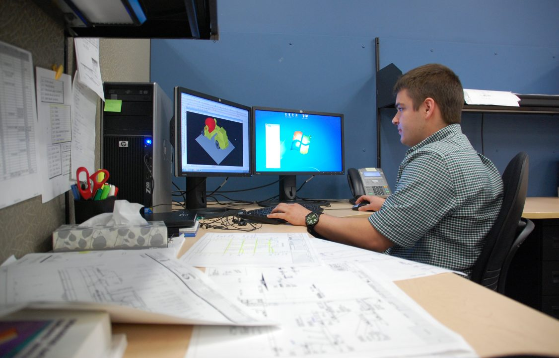 Photograph of a student in an office working on a 3d model