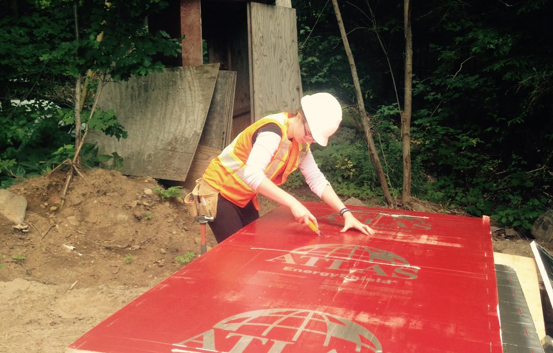 Photograph of a student cutting a piece of wood at a construction site