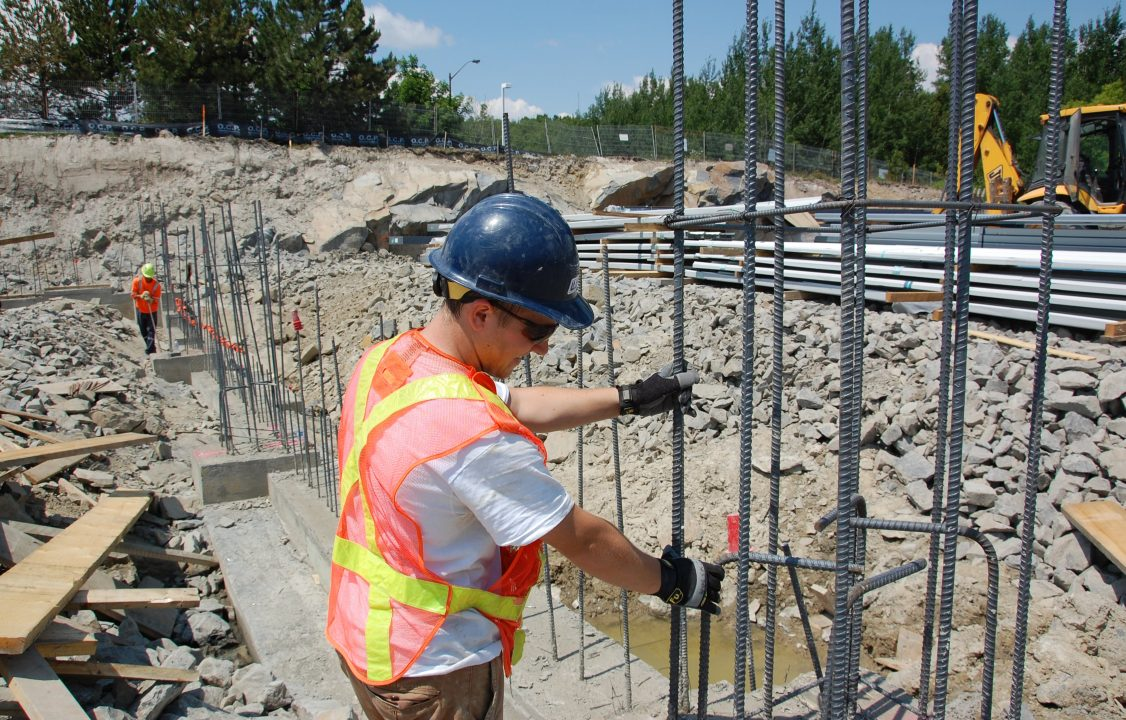 Photograph of a student setting up bars of rebar at a construction site