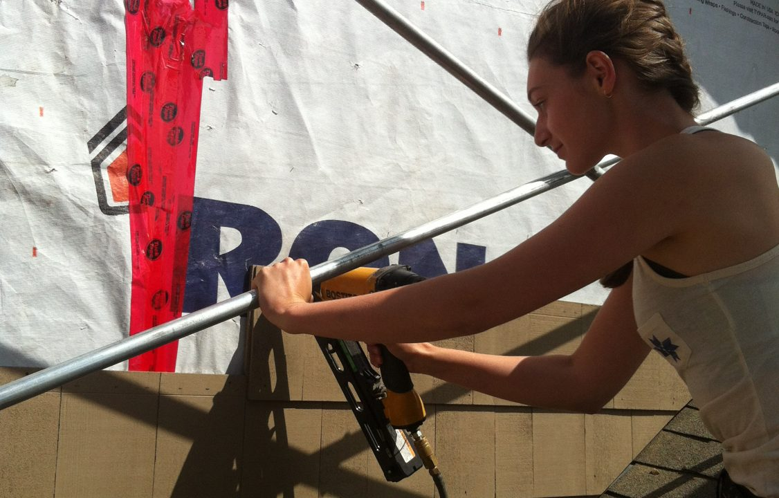 Photograph of a student bolting shingles to a wall