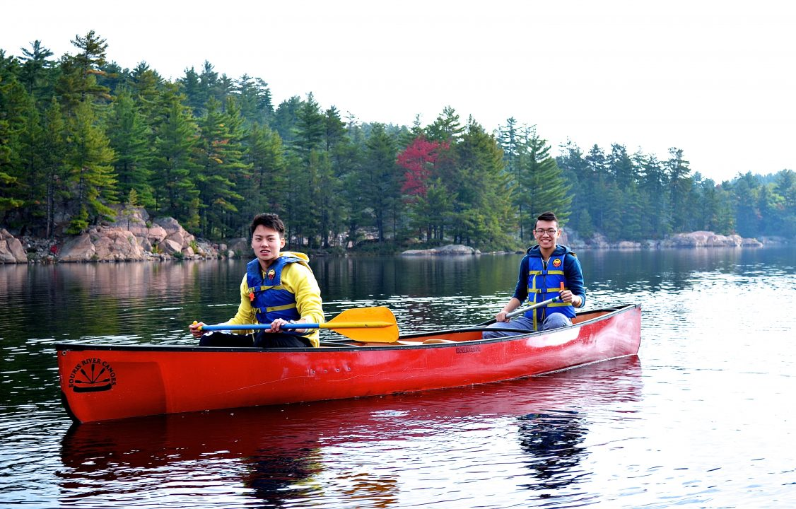 Photograph of two students in a canoe going down a river