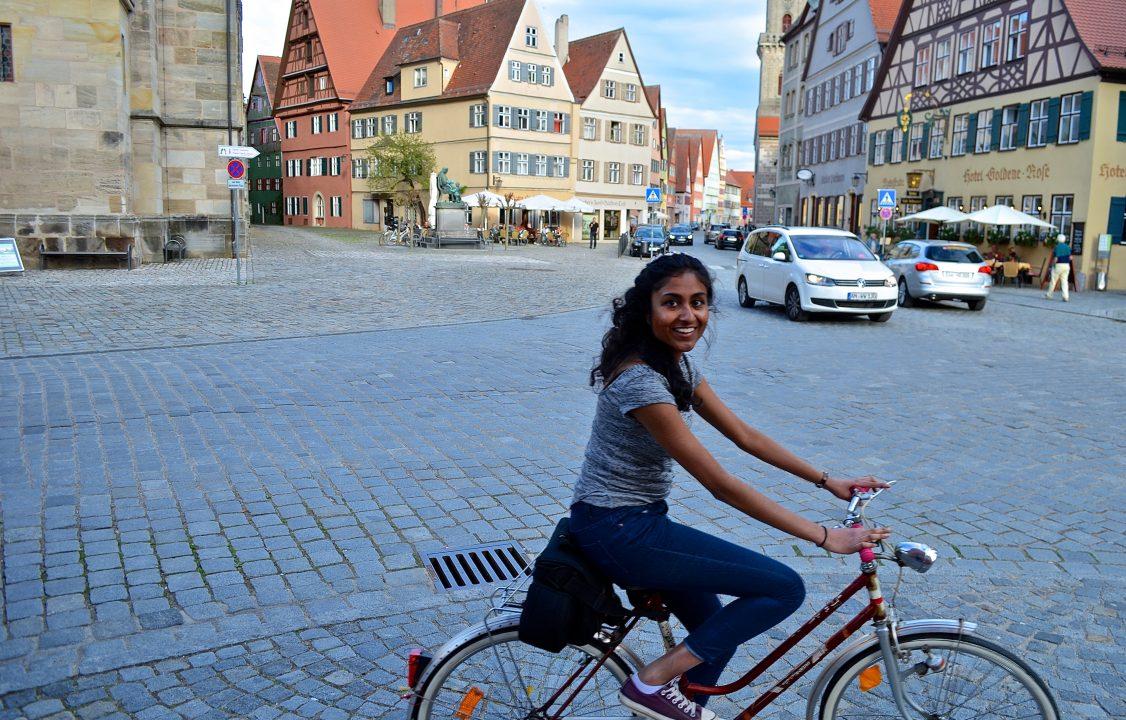 Photograph of a student biking in a cobblestone plaza