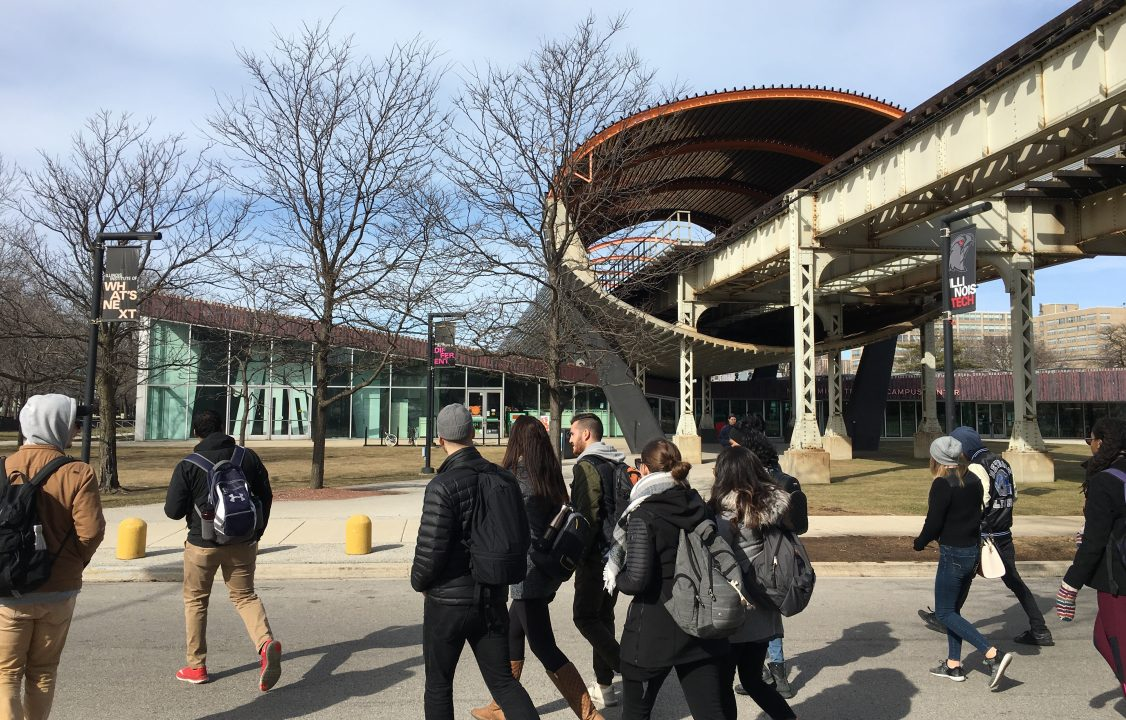 Photograph of students walking before an abstract exterior art sculpture