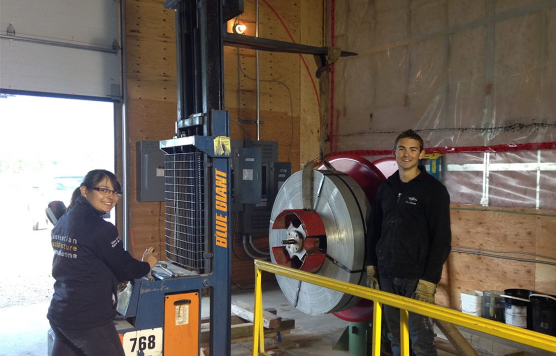 Photograph of two students standing next to a piece of equipment