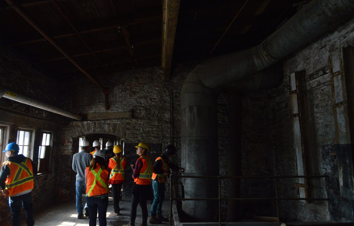 Photograph of students in safety equipment in an abandoned brewery