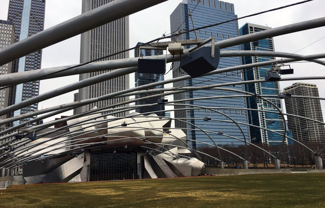 Photograph of a metal building with an overhead metal art installation above an outdoor field