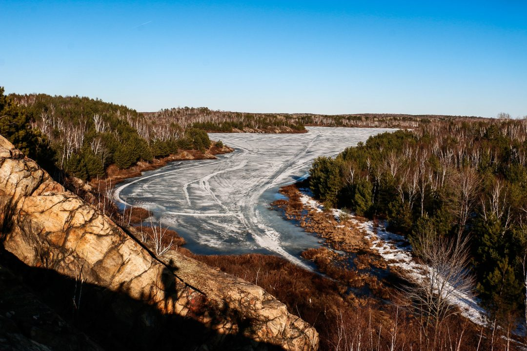 Photograph of a frozen over river from above surrounded by a forest