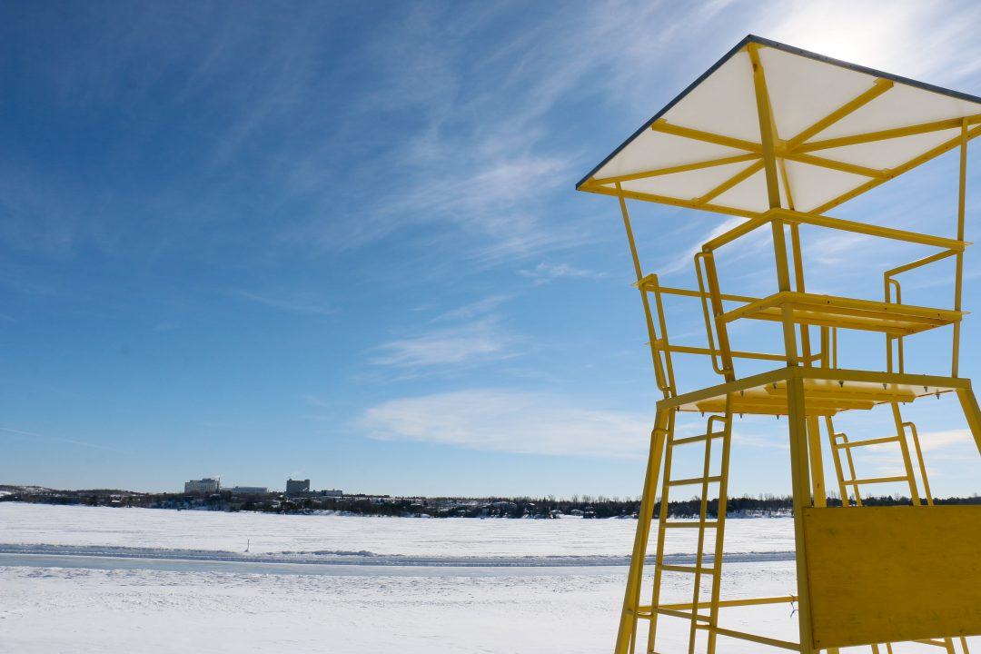 Photograph of a yellow life guard stand in front of a frozen lake