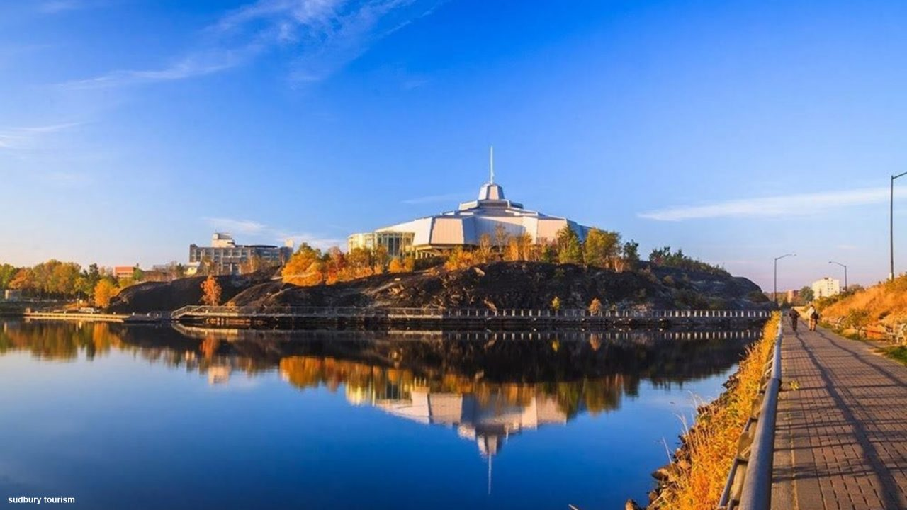 Photograph of the Science North building in Sudbury sitting on a hill behind a lake that shows it's reflection