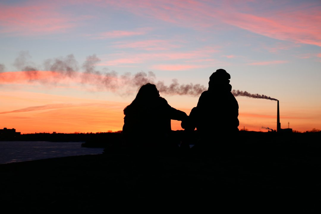 Photograph of two figures in silhouette sitting down with a sunset in the background