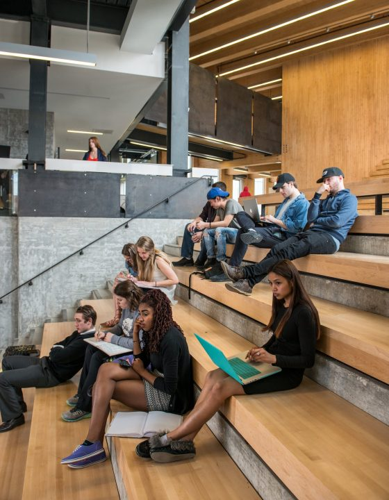 Photograph of students sitting on wooden steps in an atrium space