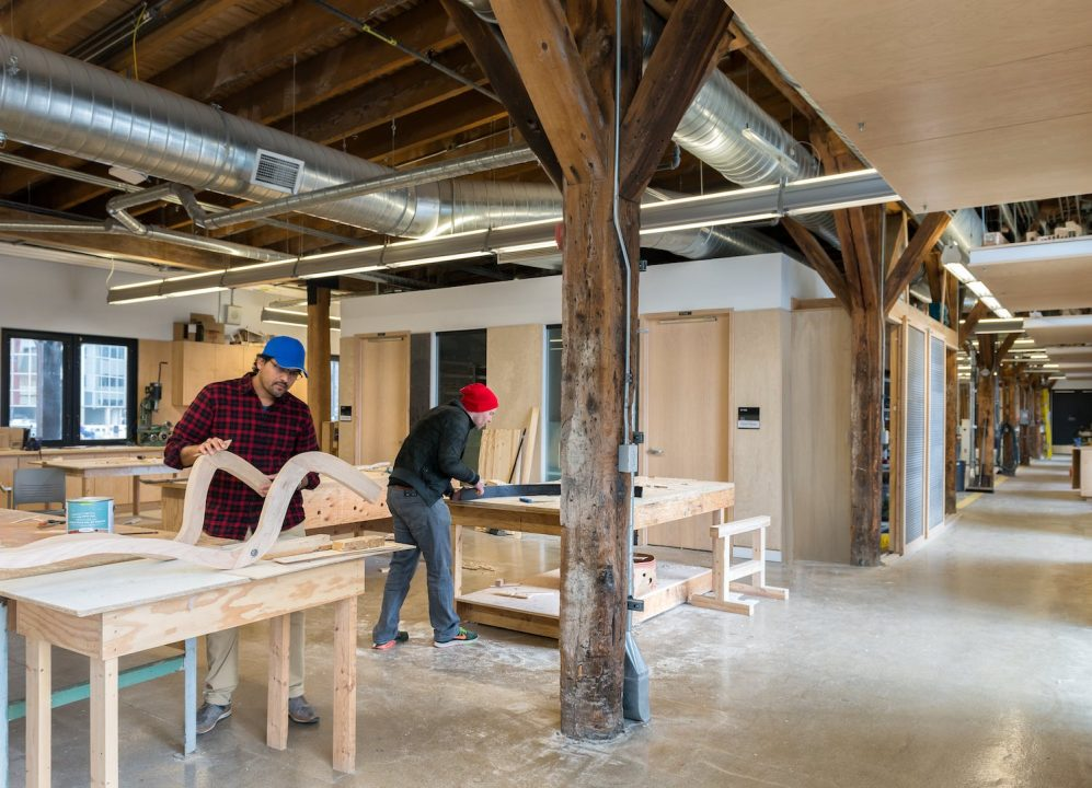 Photograph of two students working in a wood shop area