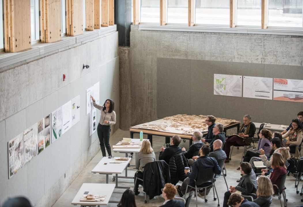 Photograph of a student presenting a poster to a larger group in the crit pit